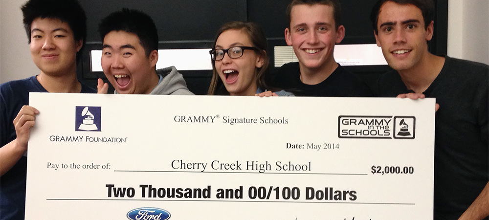 CCHS Orchestra - Students holding a check from the Grammy Signature Schools